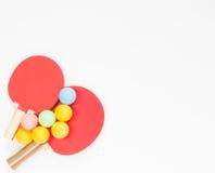 Fondo del deporte Estafas rojas del ping-pong y bolas varicolored Endecha plana, visión superior Foto de archivo