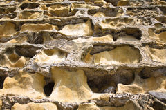Fondo del diseño de la textura del adorno del modelo de agujeros de la erosión de la pared de piedra Foto de archivo libre de regalías