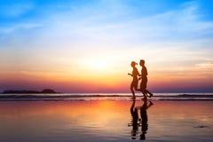 Fondo del entrenamiento, dos personas que activan en la playa Imagenes de archivo