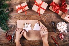 Fondo del envoltorio para regalos Manos femeninas que empaquetan decoraciones hechas a mano de la Navidad al regalo de Navidad en Fotos de archivo libres de regalías