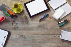 Fondo del escritorio de oficina con la tableta, el teléfono elegante y la taza de café Visión desde arriba con el espacio de la c