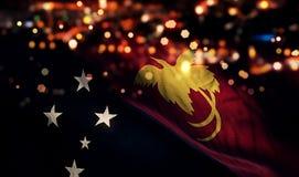 Fondo del extracto de Bokeh de la noche de la luz de la bandera nacional de Papúa Nueva Guinea Imágenes de archivo libres de regalías