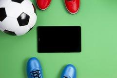 Fondo del fútbol del fútbol Vista superior de dos zapatos de los jugadores de fútbol, balones de fútbol y tabletas en fondo verde imagen de archivo