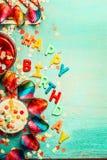 Fondo del feliz cumpleaños con las letras, decoración roja, torta y bebidas, visión superior, lugar para el texto, vertical Imagen de archivo