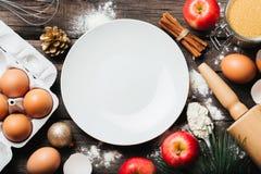 Fondo del forro de Navidad con los ingredientes para la empanada de manzana, las herramientas de la cocina y las decoraciones que fotografía de archivo
