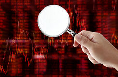 Fondo del grafico del mercato azionario con l'ingrandimento della tenuta della mano Immagini Stock