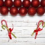 Fondo del invierno de la Navidad con la bola del juguete del Año Nuevo o chucherías y caramelo rojos en el tablero blanco de made fotografía de archivo libre de regalías