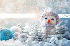Fondo del invierno de la Navidad con un pequeño muñeco de nieve y los ornamentos de la Navidad Feliz Año Nuevo y Feliz Navidad Imagen de archivo libre de regalías