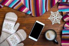Fondo del invierno: manoplas, una taza de café caliente y un smartphone Fotos de archivo