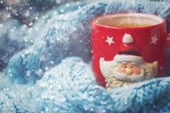 Fondo del invierno - taza roja con Papá Noel y la bufanda de lana Imagen de archivo libre de regalías
