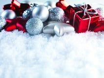 Fondo del invierno y de la Navidad El chispear hermoso decoración de plata y roja de la Navidad en un fondo blanco de la nieve Imagen de archivo libre de regalías