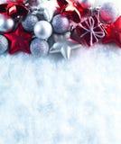 Fondo del invierno y de la Navidad El chispear hermoso decoración de plata y roja de la Navidad en un fondo blanco de la nieve Fotografía de archivo libre de regalías