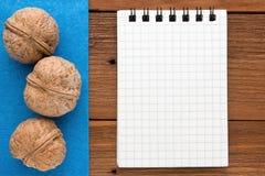 Fondo del menú Cocinero Book Cuaderno de la receta con las nueces en un fondo azul y un tablero de madera Foto de archivo