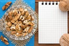 Fondo del menú Cocinero Book Cuaderno de la receta con las nueces en un fondo azul y un tablero de madera Imagenes de archivo