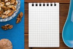 Fondo del menú Cocinero Book Cuaderno de la receta con las nueces en un fondo azul y un tablero de madera Imágenes de archivo libres de regalías