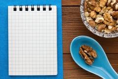 Fondo del menú Cocinero Book Cuaderno de la receta con las nueces en un fondo azul y un tablero de madera Fotos de archivo
