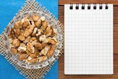 Fondo del menú Cocinero Book Cuaderno de la receta con las nueces en un fondo azul y un tablero de madera Fotos de archivo libres de regalías