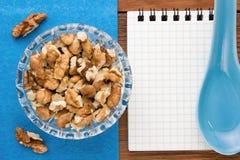 Fondo del menú Cocinero Book Cuaderno de la receta con las nueces en un fondo azul y un tablero de madera Imagen de archivo libre de regalías