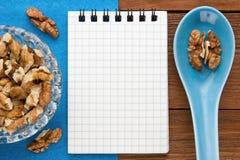 Fondo del menú Cocinero Book Cuaderno de la receta con las nueces en un fondo azul y un tablero de madera Fotografía de archivo libre de regalías