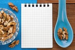 Fondo del menu Cuoco Book Taccuino di ricetta con le noci su un fondo blu e su un bordo di legno immagini stock libere da diritti