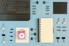 Fondo del negocio con el lugar para el texto En una superficie azul brillante, los clips de papel, los clips de papel y un cuader Imagen de archivo libre de regalías