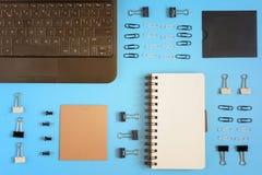 Fondo del negocio con el lugar para el texto En una superficie azul brillante, los clips de papel, los clips de papel y un cuader Fotografía de archivo