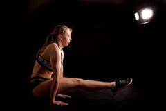 Fondo del negro de la actitud de la yoga de Tittibhasana de la muchacha del gimnasta del deporte Imagenes de archivo