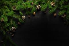 Fondo del nuovo anno e di Natale Ramo dell'albero di Natale su un fondo nero Coni e giocattoli dell'pelliccia-albero Vista da sop Immagini Stock Libere da Diritti