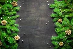Fondo del nuovo anno e di Natale Ramo dell'albero di Natale su un fondo nero Coni e giocattoli dell'pelliccia-albero Vista da sop immagine stock libera da diritti