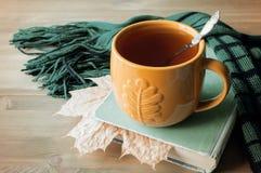Fondo del otoño con la taza de té, de libro viejo y de bufanda caliente en el fondo de madera Todavía del otoño vida Foto de archivo