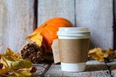 Fondo del otoño con las hojas secas y la taza de café de papel caliente en la tabla de madera Fotografía de archivo