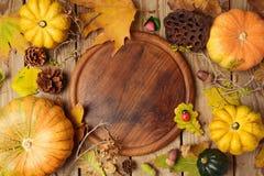 Fondo del otoño con las hojas y la calabaza de la caída sobre la tabla de madera Imagen de archivo