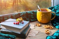 Fondo del otoño Taza de té, de galletas, de libros viejos y de tela escocesa en alféizar y escena del otoño al aire libre Foto de archivo