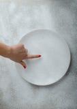 Fondo del piatto di Snowy con una mano della donna Fotografie Stock