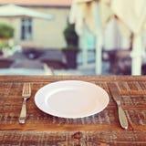 Fondo del restaurante con la placa y los cubiertos vacíos Imagen de archivo