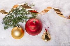 Fondo del `s del Año Nuevo Bolas de la Navidad, campana amarilla y rama de árbol de navidad con las bayas de la baya en nieve Fotografía de archivo libre de regalías