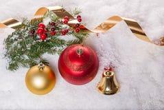 Fondo del `s del Año Nuevo Bolas de la Navidad, campana amarilla y rama de árbol de navidad con las bayas de la baya en nieve Imágenes de archivo libres de regalías