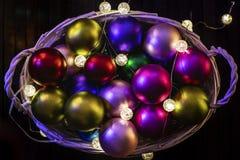 Fondo del `s del Año Nuevo Composición de la Navidad con la cesta, bolas multicoloras de la Navidad, un fondo negro fotos de archivo