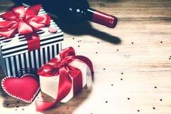 Fondo del ` s de la tarjeta del día de San Valentín del St con los presentes y la botella de vino rojo Gre Fotos de archivo