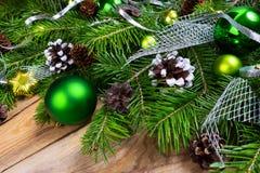 Fondo del saludo del día de fiesta de la Navidad con los ornamentos verdes Fotos de archivo libres de regalías
