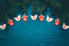 Fondo del saludo de la Feliz Navidad y de la Feliz Año Nuevo con las ramas de árbol de abeto y los juguetes de madera Imagenes de archivo