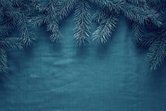 Fondo del saludo de la Feliz Navidad y de la Feliz Año Nuevo con las ramas de árbol de abeto y los juguetes de madera Foto de archivo