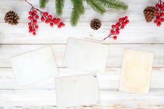 Fondo del tema de la Navidad con el papel en blanco de la foto y elementos del adornamiento en la tabla de madera blanca Imagen de archivo libre de regalías