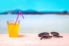 Fondo del verano con el cóctel y las gafas de sol amarillos en la toalla en la playa Vista al mar borrosa hermosa del paraíso Foto de archivo