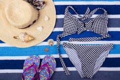 Fondo del verano con el sombrero, chancletas y el traje de baño de paja Visión superior Imagenes de archivo