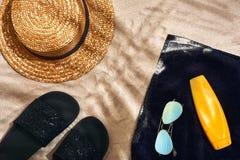 Fondo del verano con el sombrero de paja, las gafas de sol, la botella de la protección solar y chancletas Imágenes de archivo libres de regalías