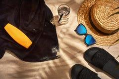 Fondo del verano con el sombrero de paja, las gafas de sol, la botella de la protección solar y chancletas Fotografía de archivo libre de regalías