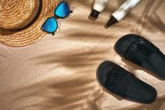Fondo del verano con el sombrero de paja, las gafas de sol, la botella de la protección solar y chancletas Imagen de archivo