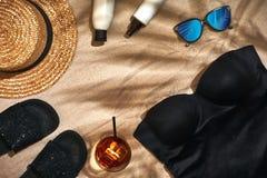 Fondo del verano con el sombrero de paja, las gafas de sol, la botella de la protección solar y chancletas Fotos de archivo