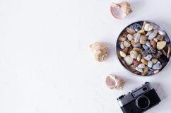 Fondo del verano con la cámara, las cáscaras y los guijarros del mar imagenes de archivo